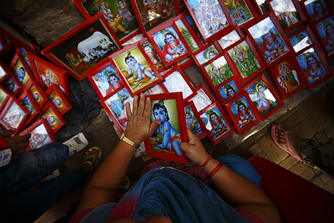 A devotee cleans a portrait of Krishna as she makes a purchase from a vendor during the Krishna Janmasthami festival in Lalitpur.