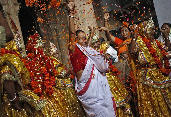 A woman throws flower petals and dances with widows dressed as Radha, during celebrations to mark Janmashtami festival at the Meera Sahavagini ashram in Vrindavan in Uttar Pradesh
