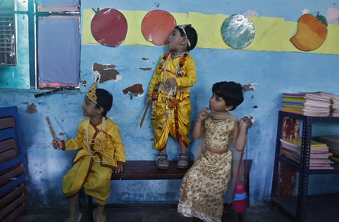Boys dressed as Krishna and a schoolgirl wait for their performance to start inside a classroom during the celebrations to mark Janmashtami in New Delhi.