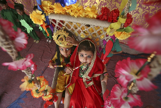 Schoolchildren dressed as Krishna and Radha take part in celebrations to mark the Janmashtami festival in Jammu.