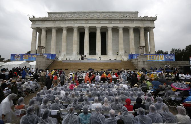 Attendees wear rain coats during a storm at a ceremony marking the 50th anniversary of Martin Luther King Junior's I have a dream speech on the steps of the Lincoln Memorial in Washington
