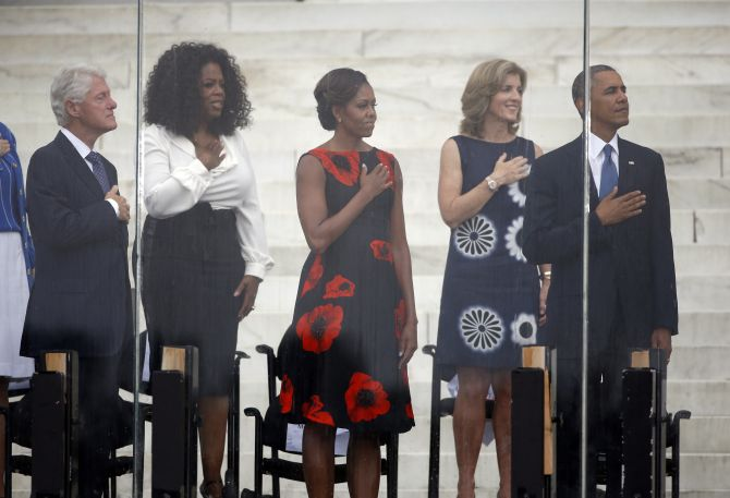 Former US president Bill Clinton (L-R), Oprah Winfrey, US first lady Michelle Obama, Caroline Kennedy, and US President Barack Obama are pictured during the national anthem at a ceremony marking the 50th anniversary of Martin Luther King's I have a dream speech on the steps of the Lincoln Memorial in Washington