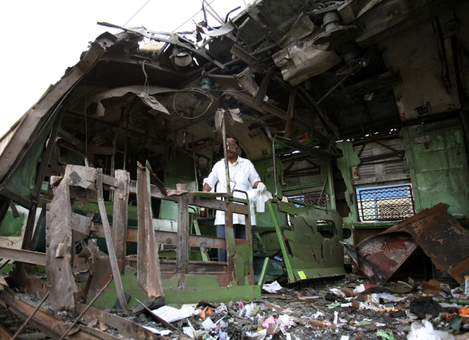 A forensic officer examines a damaged railway train compartment hit by serial blasts in Mumbai in July 2006
