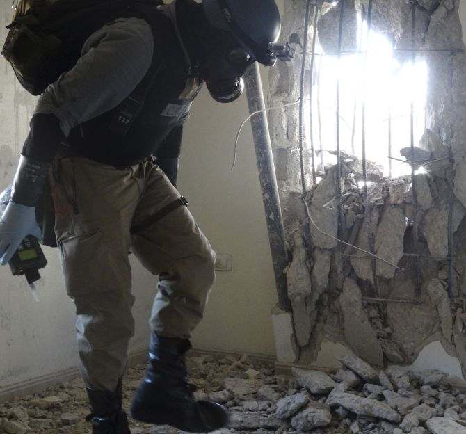 A UN chemical weapons expert, wearing a gas mask, inspects one of the sites of an alleged chemical weapons attack in the Damascus' suburb of Zamalka