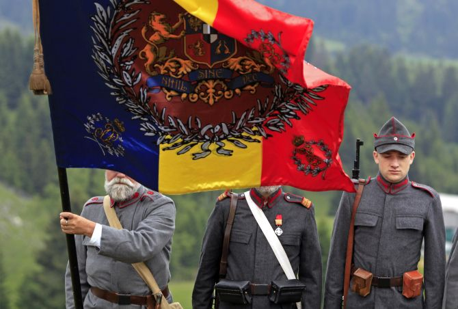 Participants dressed in 1916 Romanian troops uniforms stand behind their banner before the re-enactment of a battle in World War One at a Military History festival organised in Fundata village near Bucharest