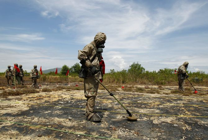 Soldiers detect Unexploded Ordnance (UXO) and defoliant Agent Orange during the launch of the environmental remediation of dioxin contamination project, in Vietnam's central Da Nang City