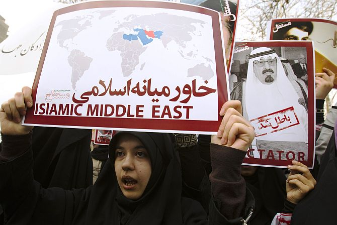 Women protesters hold a placard and a poster of Saudi Arabia's King Abdullah during a protest