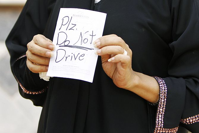 Female driver Azza Al Shmasani displays a note, which according to her, was placed on her car by an unknown person, in Saudi Arabia
