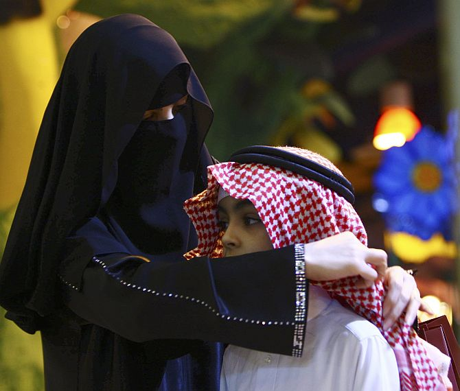 A Saudi woman adjusts her son's headdress at Al-Faisaliya mall after the breaking of fast, or Iftar, in Riyadh