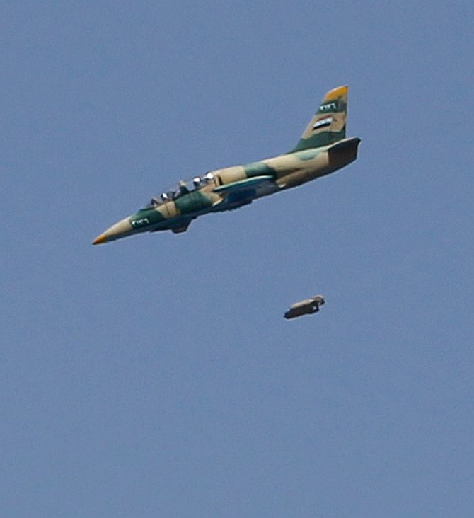 A Syrian Air Force fighter jet drops bombs on the El Edaa district of Syria's northwestern city of Aleppo
