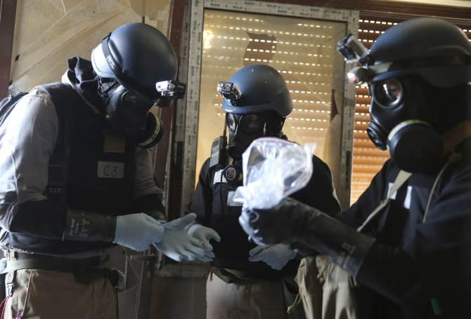 A UN chemical weapons expert, wearing a gas mask, holds a plastic bag containing samples from one of the sites of an alleged chemical weapons attack in the Ain Tarma neighbourhood of Damascus
