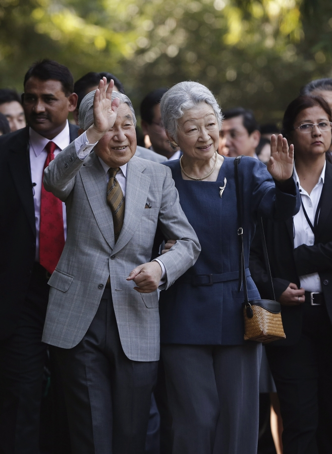 Japan's Emperor Akihito and Empress Michiko wave towards the crowd during their visit to the Lodhi Gardens in New Delhi