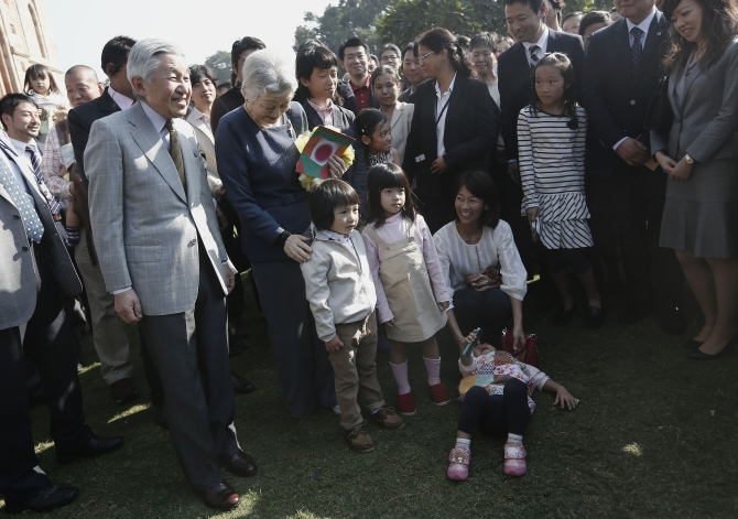 Emperor Akihito and Empress Michiko pose for a picture with children