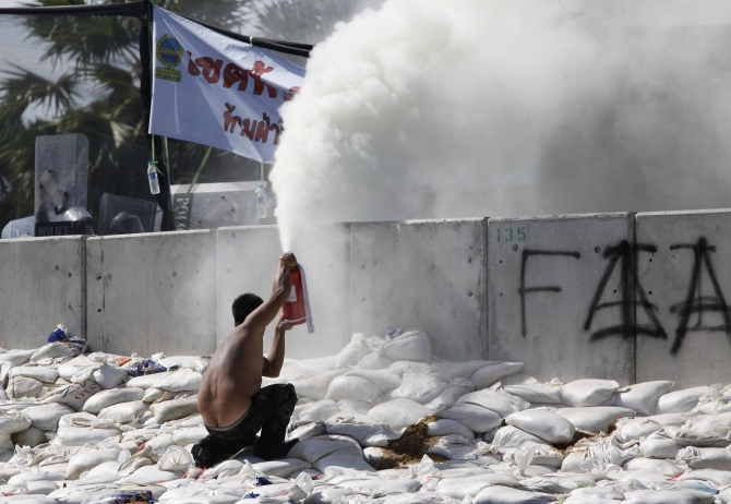 An anti-government protester uses a fire extinguisher during clashes with police near the Government House in Bangkok