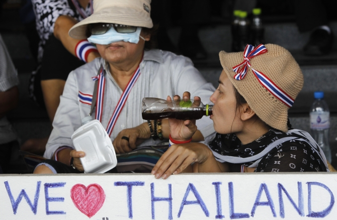 An anti-government protester drinks coffee while holding a sign during a rally at a government complex in Bangkok