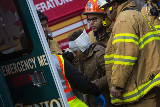 A woman is taken to an ambulance at the site of a Metro-North train derailment in the Bronx borough of New York