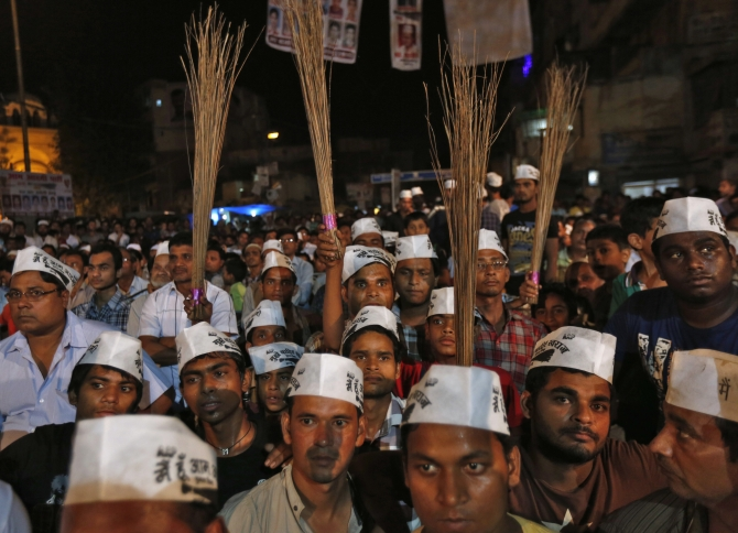 AAP supporters hold brooms, the party's symbol, during a public meeting in New Delhi
