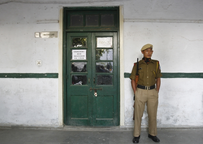 A security personnel stands guard outside the sealed room containing electronic voting machines in New Delhi