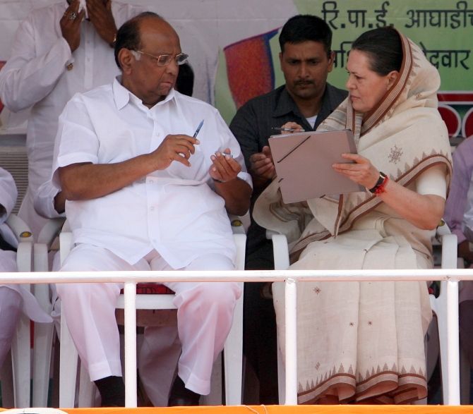 Congress president Sonia Gandhi talks to Nationalist Congress Party chief Sharad Pawar at an election rally