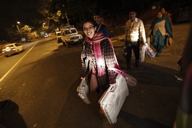 Polling officers carry electronic voting machines as they leave a polling station at the end of polls, during the state assembly election in New Delhi