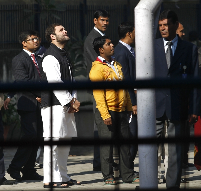 Rahul Gandhi waits in a queue to cast his vote outside a polling station during the state assembly elections in New Delhi