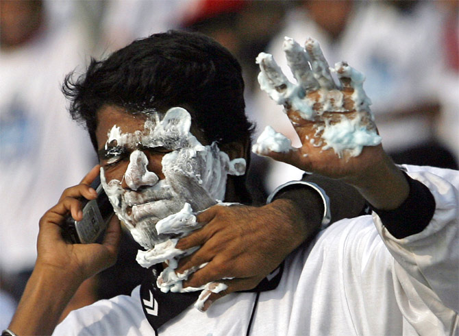 A man speaks on a mobile phone as another playfully applies shaving cream