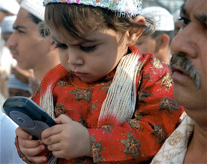 A child plays with a mobile phone during a festival