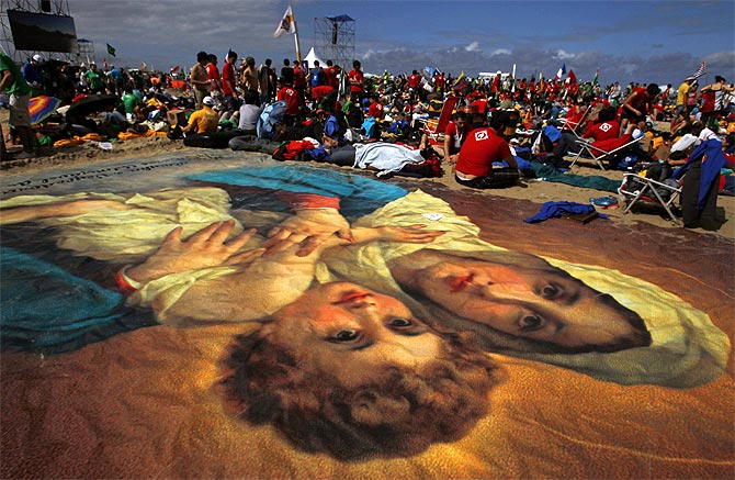 -Catholic faithful camp out next to a giant image of the Virgin Mary and baby Jesus on Copacabana Beach to participate in the all-night vigil before Pope Francis gives mass to those attending the World Youth Day, in Rio de Janeiro