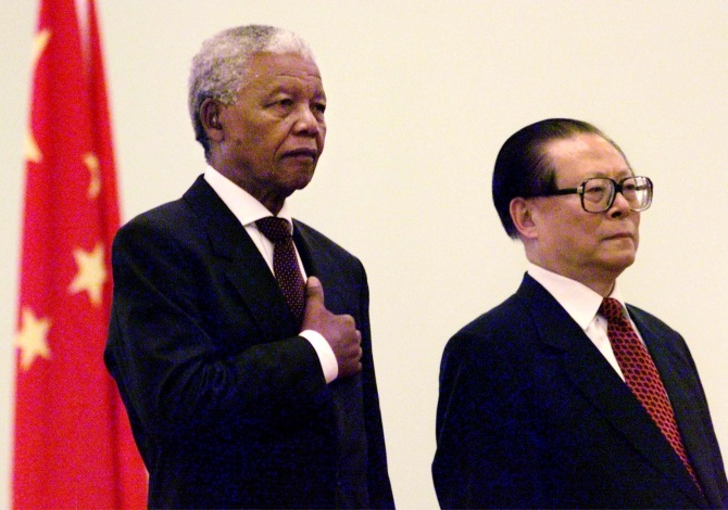 South African President Nelson Mandela escorted by the then Chinese President Jiang Zemin listens to the South African national anthem during a welcoming ceremony at the Great Hall of the People in Beijing in May 1999