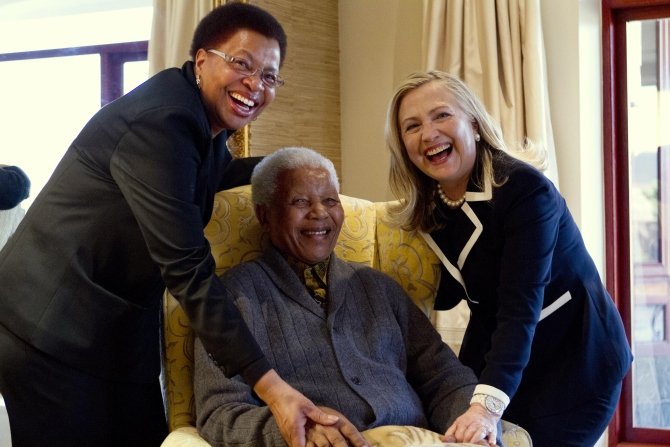 Hillary Clinton poses for a photograph with Nelson Mandela and his wife Graca Machel at his home.