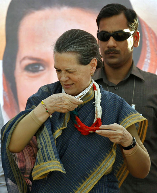 Congress President Sonia Gandhi tries to take off a garland presented to her by a supporter as she arrives to address a rally ahead of the state elections in Dungarpur, Rajasthan