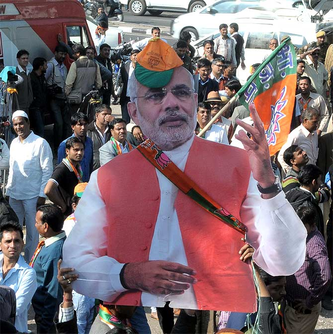 BJP supporters carry a cut out of their prime ministerial candidate Narendra Modi as they celebrate their thumping victory in Rajasthan.