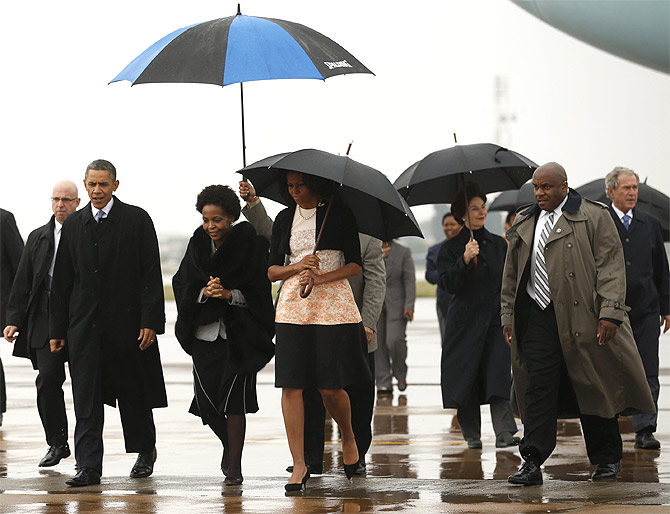 US President Barack Obama and First Lady Michelle Obama are escorted upon their arrival on Air Force One to attend a memorial service for Nelson Mandela