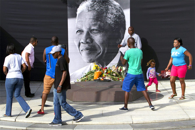 eople walk around a memorial for former South African President Nelson Mandela as they lay wreaths of flowers and take photos during a joint session of parliament held in tribute to him in Cape Town