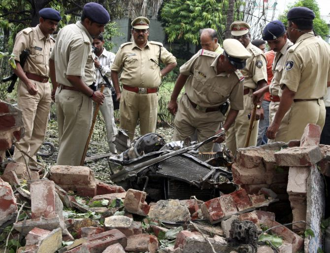 Police personnel search for evidence near the site of a bomb blast in Ahmedabad in 2008.