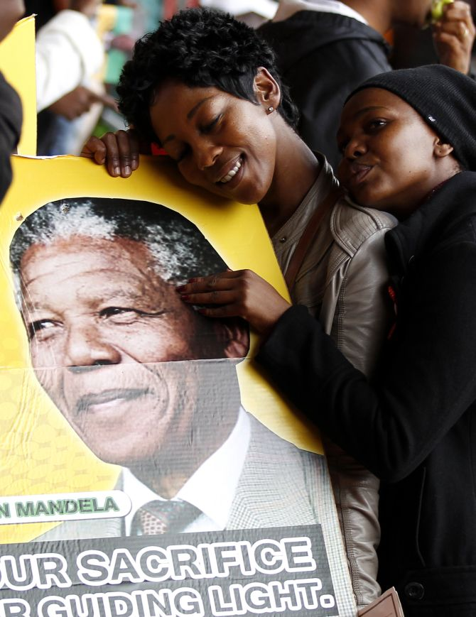 People pose for a picture while holding a placard during the national memorial service for former South African President Nelson Mandela at the First National Bank (FNB) Stadium, also known as Soccer City, in Johannesburg