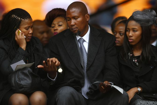 Mandla Mandela (C), eldest grandson of former South African President Nelson Mandela, attends the official memorial service for Nelson Mandela at the First National Bank stadium, also known as Soccer City, in Johannesburg