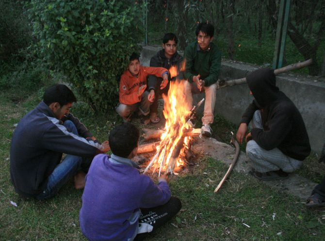 Kashmiri boys warm themselves around a fire during a cold day in Srinagar