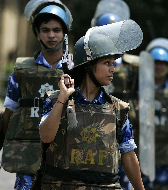 A woman personnel of the Rapid Action Force marches along with male counterparts at a police training school in Kolkata