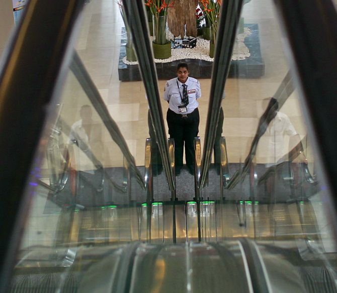A female private security personnel stands guard between escalators inside a shopping mall in Mumbai.