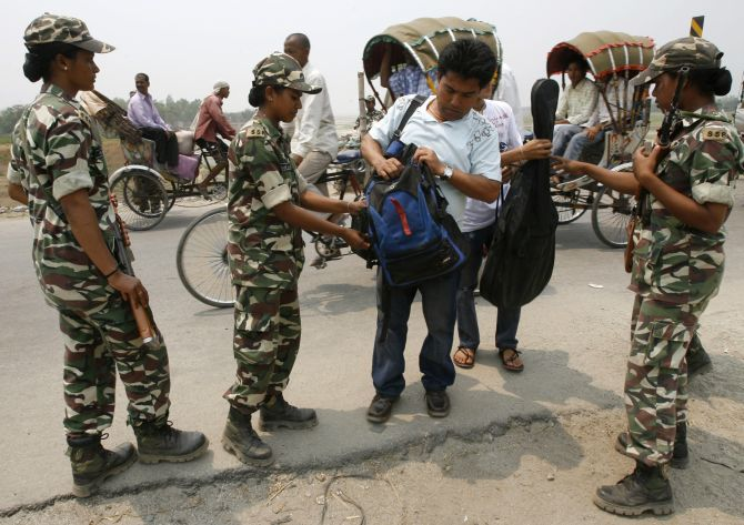 Female paramilitary soldiers check the belongings of a tourist near the border with Nepal close to Siliguri.