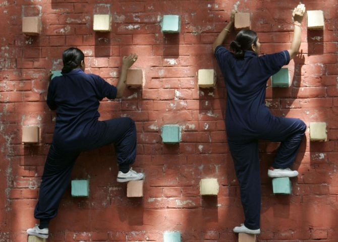 Female members of the Rapid Action Force perform an obstacle climbing exercise at a police training school in Kolkata.