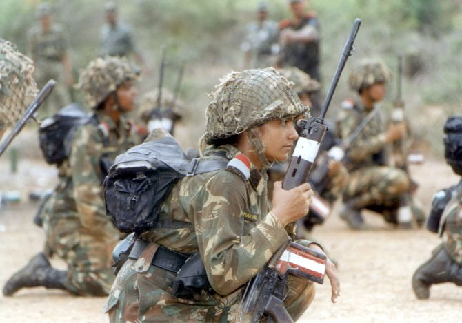 Female soldiers hold transistor radios during a weapons training session at an army camp near Chennai.