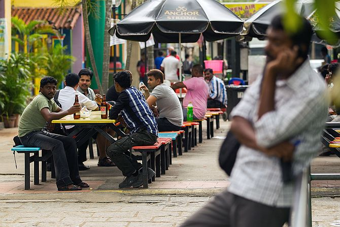 Foreign workers walk around Little India