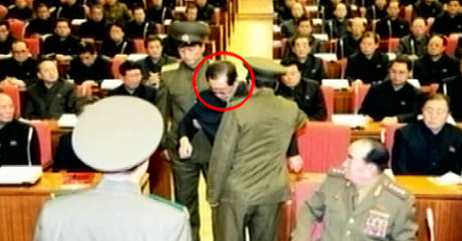 Jang (circled) being dragged from a meeting by the police in Pyongyang as other members look on.