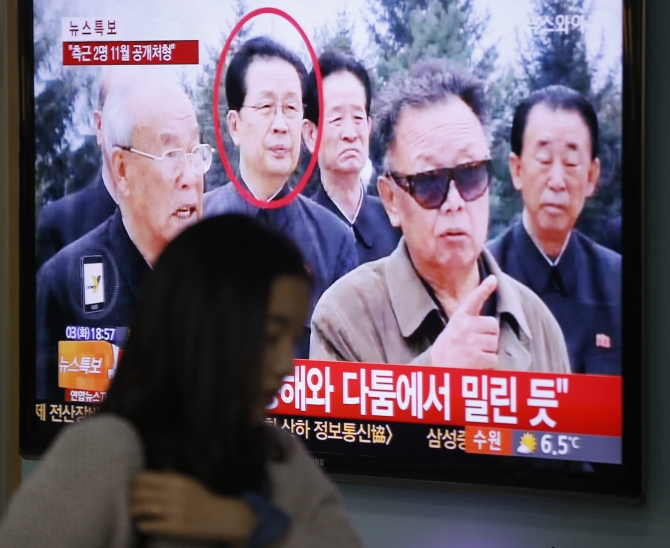 A woman walks past a television showing a report on Jang Song Thaek at a railway station in Seoul