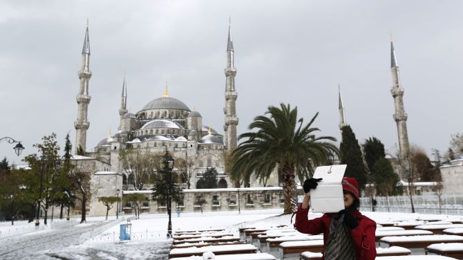 A foreign tourist, with the Ottoman-era Sultanahmet mosque, known as the Blue mosque in the background, takes souvenir photos as she strolls in snow-covered Sultanahmet square in Istanbul
