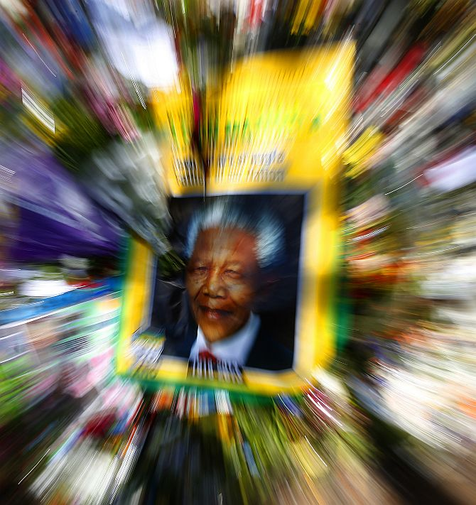 A poster depicting a photo of former South African President Nelson Mandela is seen among flowers outside of Mandela's house in Johannesburg