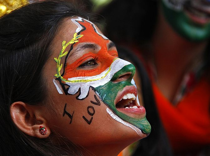A girl, with her face painted in the colours of India, celebrates Independence Day