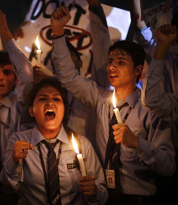 School children shout slogans as they hold candles during a candle light vigil to mark the first anniversary of the Delhi gang rape